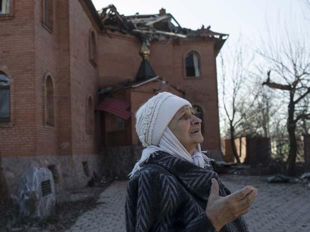 Senhora chora ao ver igreja destruída nesta segunda-feira (9) em Donetsk, região separatista no leste da Ucrânia (Foto: REUTERS/Marko Djurica)