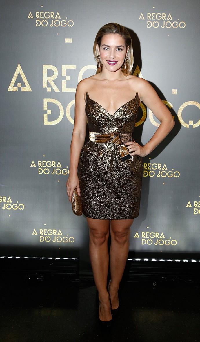Monique Alfradique exibe pernões em vestido curtinho dourado, com cintura marcada (Foto: Raphael Dias/Gshow)