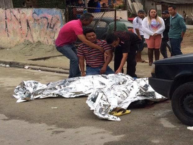 Homem chora ao ver corpo de baleado na tarde desta quarta-feira (8) na rua Gumercindo Coelho em Mogi das Cruzes (Foto: Luis Corvini/ TV Diário)
