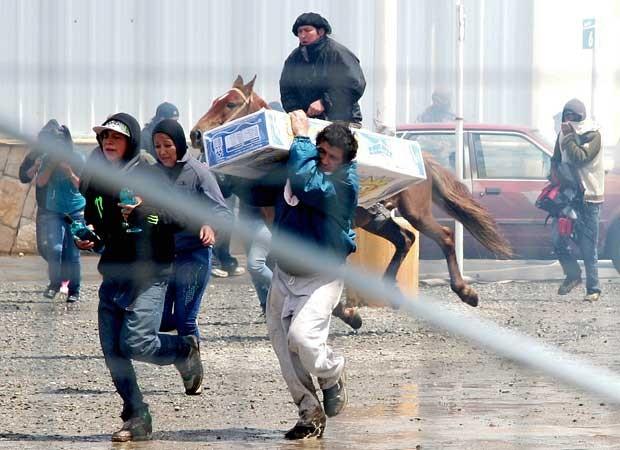 Pessoas correm com itens roubados de supermercado em Bariloche, Argentina, nesta quinta-feira (20) (Foto: AFP)