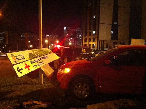 Um motorista perdeu o controle do carro, subiu a calçada e derrubou uma placa nova da Copa, em Brasília, na noite desta terça-feira (11). Ninguém se feriu. O acidente ocorreu por volta das 20h30, na via N3 (Foto: Káthia Mello/G1)