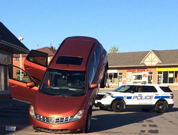 Motorista ficou com o veículo suspenso ao atingir das duas barras de proteção (Foto: Reprodução/Twitter/Peel Regional Police)