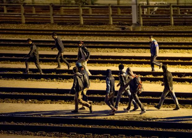Imigrantes são vistos andando nos trilhos do terminal do Eurotúnel em Calais, na França, nesta terça-feira (28) (Foto: Philippe Huguen/AFP)