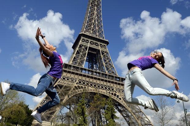 Turistas saltam em frente à Torre Eiffel, em Paris (Foto: Franck Fife/AFP)
