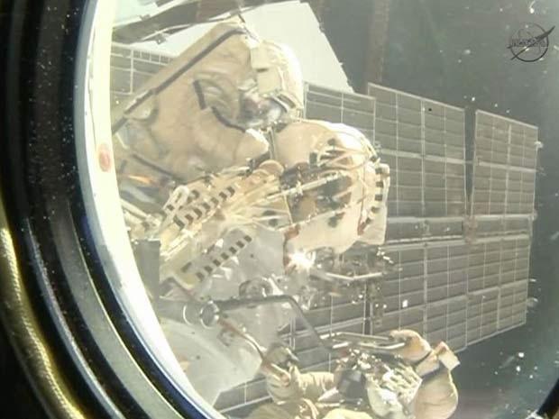 Uma câmera dentro da Estação Espacial Internacional captou caminhada espacial realizada nesta sexta-feira (27) (Foto: NASA TV)