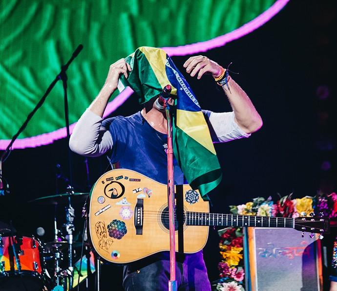 Chris Martin, envolto na bandeira do Brasil, declarou todo seu amor ao país, que visita pela quinta  vez (Foto: Breno Galtier / T4F)