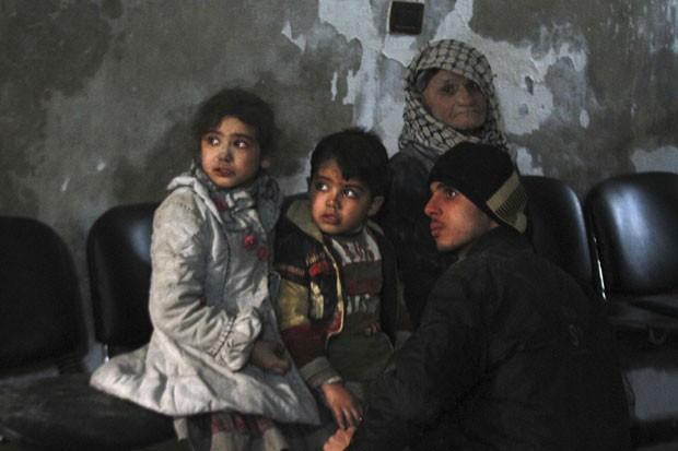 Crianças feridas aguardam tratamento em hospital em Duma, na região de Damasco, no dia 21 de dezembro, após um ataque que segundo ativistas foi feito por forças leais a Bashar al-Assad (Foto: Badra Mamet/Reuters)