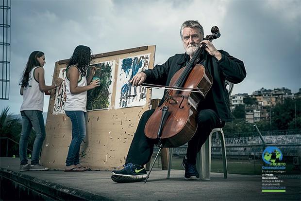 """PINTANDO  DE OUVIDO Chew  toca violoncelo enquanto duas meninas pintam,  na favela da Maré,  do Rio. """"As crianças são como esponjas""""  (Foto: Stefano Martini/ÉPOCA)"""