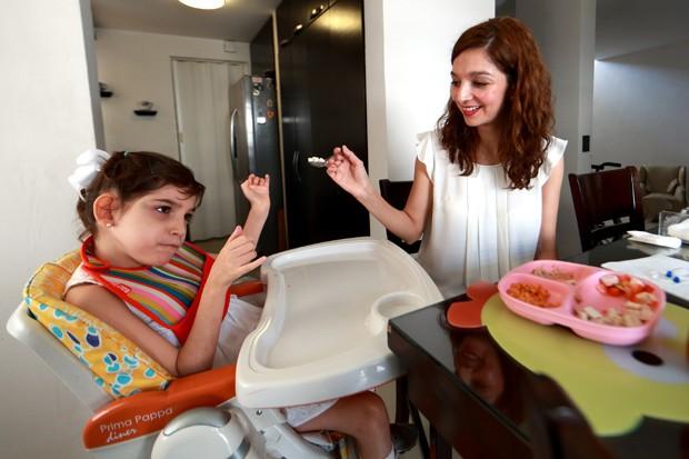 Mayela Benavides dá comida para sua filha Graciela, que sofre de epilepsia  (Foto: AFP Photo/Carlos Ramirez)