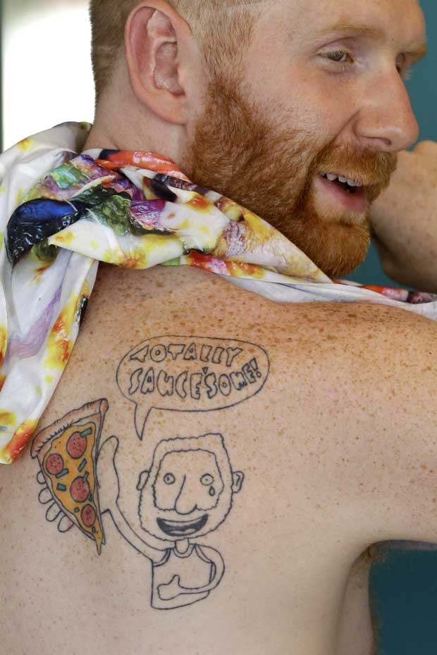 """Brian Dwyer tem tatuado nas costas uma caricatura de si mesmo comendo um pedaço de pizza com o texto """"Totally saucesome"""", outro trocadilho, que une """"muito legal"""" com """"sabor"""" (Foto: Reuters)"""