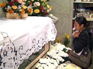 Devotos rezam diante do mausoléu onde está o caixão com o corpo da menina Izildinha (Foto: Márcio Meireles/EPTV)