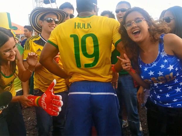 Fãs usam mão inflável para brincar com o sósia do jogador Hulk, que está de costas, durante a Fifa Fan Fest em Brasília  (Foto: Raquel Morais/G1)