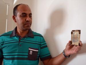 Maurício segura relíquia antiga de Padre Victor passada a ele pela mãe, também devota (Foto: Samantha Silva / G1)