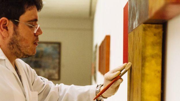 """Técnico do museu Oscar Niemeyer faz manutenção de obra de Antônio Dias. """"Sem título, 2011"""". Óleo sobre tela, 90 x 136 cm. (Foto: Marcio Pimenta Foto Series)"""