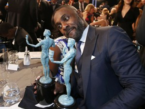 "Idris Elba sits with his two awards, one for Outstanding Performance by a Male Actor in a Television Movie or Miniseries for his role in ""Luther"" and one for Outstanding Performance by a Male Actor in a Supporting Role for his role in ""Beasts of No Nation (Foto: Lucy Nicholson/Reuters)"