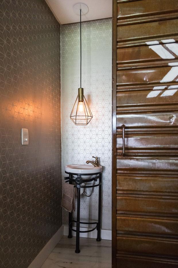 Lavabo | Para combinar com o estilo moderno do lar, a porta do lavabo foi garimpada em um ferro velho e adaptada. Luminária Lady à venda na Muma. Revestimento da Papel de Parede Anos 70. Pia e suporte garimpados em antiquário (Foto: Marcelo Donadussi/Divulgação)
