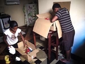 Alan e Emili abrindo cesta básica entregue por moradores (Foto: Thayná Cunha/ G1)