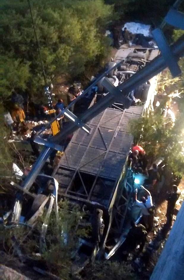 Policiais trabalham em resgate de corpos em acidente na província de Salta, na Argentina (Foto: AFP)