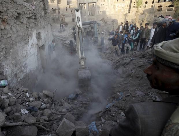 Máquina retira escombros para ajudar na busca por sobreviventes após bombardeio este sábado (19) em Sanaa, capital no Iêmen  (Foto: Mohamed al-Sayaghi/Reuters)