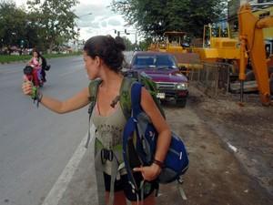 Kívia pedindo carona durante a volta ao mundo (Foto: Kívia Costa/Arquivo pessoal)