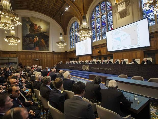 Mapa com limites territoriais no Oceano Pacífico é projetado em sessão da Corte Internacional de Justiça em Haia, Holanda. O tribunal concedeu ao Peru parte do mar sob controle do Chile, encerrando um dos litígios territoriais mais antigos do continente. (Foto: Michael Kooren/Reuters)