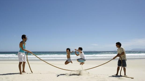 Brincadeiras de criana que ajudam os pais adultos a perderem peso e calorias Pai me crianas pulando corda (Foto: Getty Images)