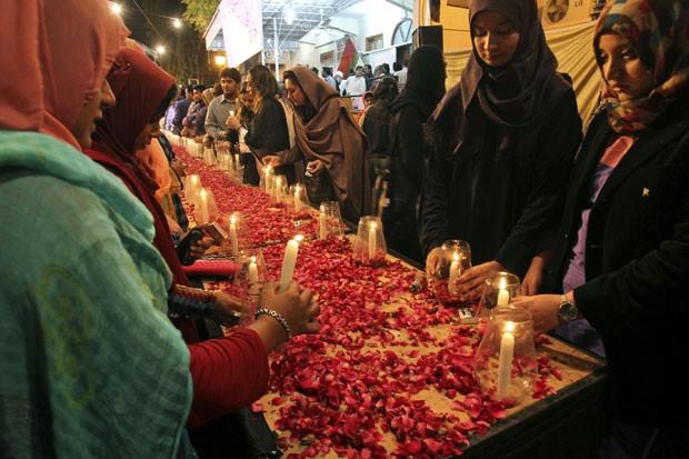 Apoiadores do movimento Mutahida Qaumi seguram velas em Karachi em  vigília pelas vítimas do massacre (Foto: AP Photo/Fareed Khan)