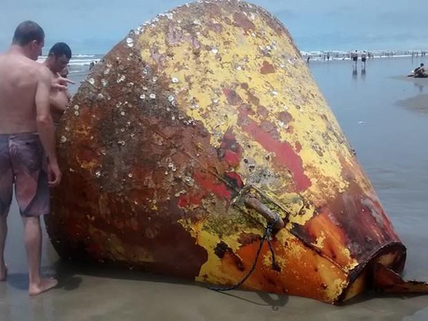 Banhistas observam grande objeto que encalhou em Praia Grande, SP (Foto: Luciane Knapick/VC no G1)