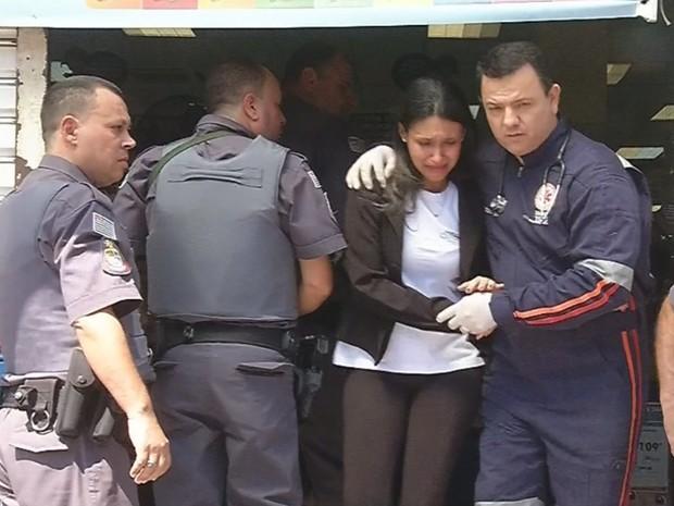 Mulher feita refém é retirada abalada de dentro da loja (Foto: Reprodução / TV TEM)