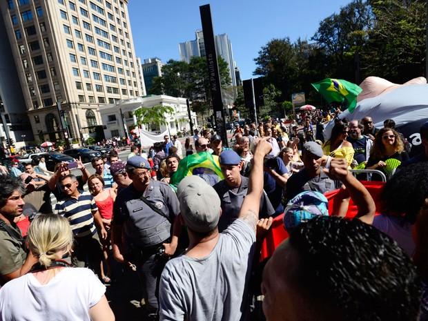 Policiais separam os grupos contra (à frente) e a favor (ao fundo) do ato com o boneco inflável de Lula (esvaziado, à direita) na Avenida Paulista neste domingo (Foto: Cris Faga/Fox Press Comunicação/Estadão Conteúdo)