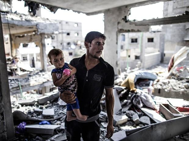 5/8/2014 - Palestino com bebê no local onde ficava sua casa em Beit Hanun, cidade destruída no conflito entre Hamas e Israel  (Foto: AFP Photo/Marco Longari)