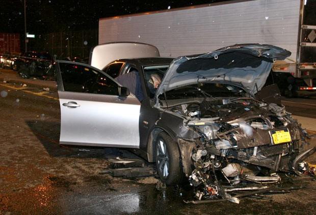 Policial observa os destroços do carro logo após o acidente neste domingo (3) (Foto: AP)