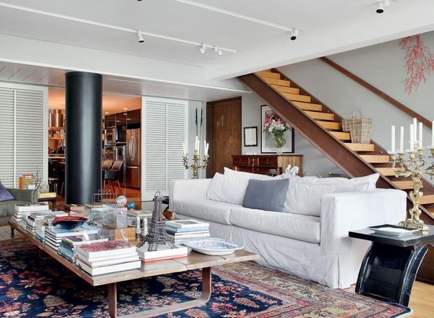 apartamento-duplex-Fernanda-Pessoa-de-Queiroz-sala-de-estar-sofá-capa-escada-mesa-de-centro-tapete-livros (Foto: Denilson Machado/MCA Estúdio/Editora Globo)