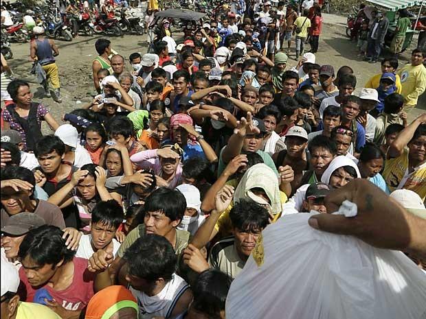 Filipinos afetados pelo tufão enfrentam grandes filas para conseguir kits de socorro e alimentos. (Foto: Bullit Marquez / AP Photo)