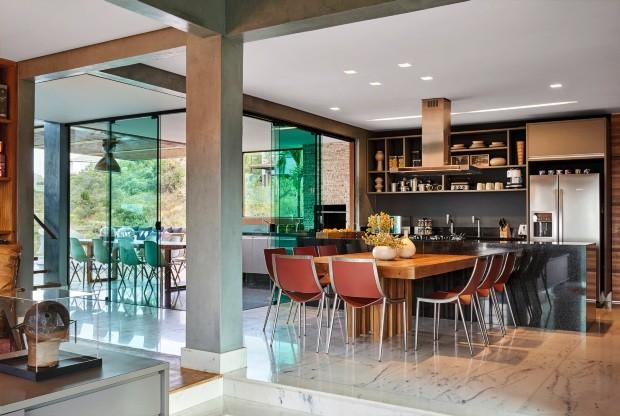 Integração A cozinha aberta para o jantar se conecta com varanda gourmet separada por painéis de vidro deslizantes. Parede com textura grafite. Mesa de jantar de peroba-do-campo de demolição  (Foto: Jomar Bragança / Divulgação)