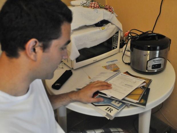 Estudante se divide entre livros e utensílios para preparar a comida,  em Valinhos (Foto: Giulia Cirilo / G1 Campinas)