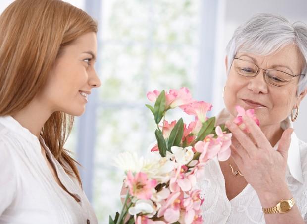 Mulher entregando flores para a sogra (Foto: Shutterstock)