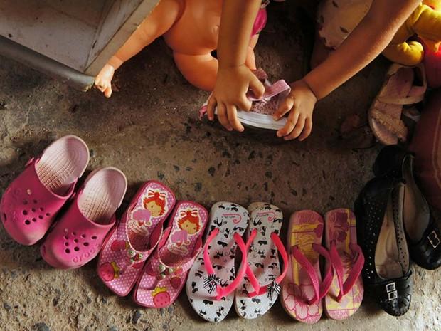 Menina organiza pares de chinelo em Paraisópolis (Foto: Glauco Araújo/G1)