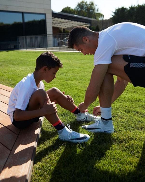 Cristiano Ronaldo amarra as chuteiras do filho mais velho, Jr. (Foto: Reprodução/Instagram)