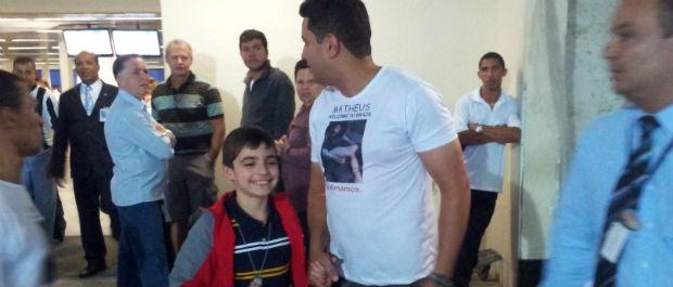 Garoto Matheus com o pai Carlos Eduardo na saída do aeroporto (Foto: Leandro Nossa / G1 ES)