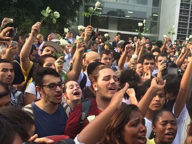 Estudantes seguram botão de rosa branca na saída da Alesp (Foto: Lívia Machado/G1)