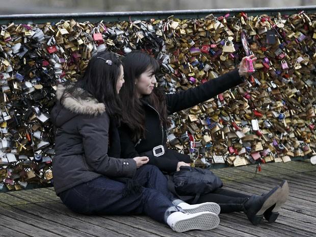 Garotas tiram foto na ponte repleta de cadeados (Foto: Charles Platiau/Reuters)