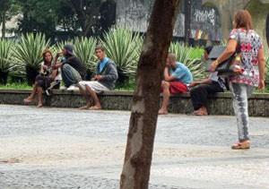 Mulher caminha ao lado de usuários de crack na Praça da Sé, na região central (Foto: Paulo Toledo Piza/G1)