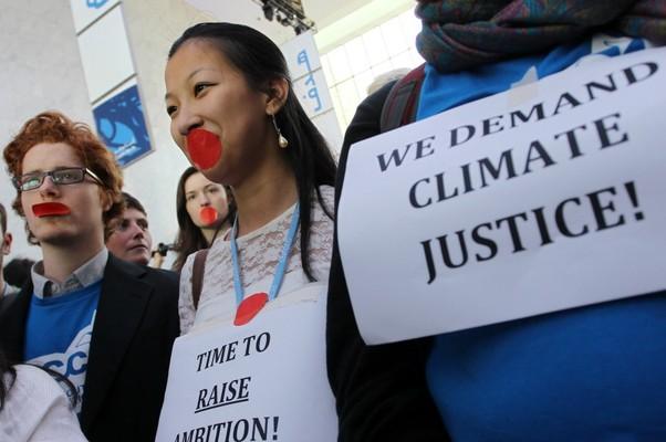 Ativistas protestam em Doha, Catar, contra países que não querem manter o Protocolo de Kyoto, como Estados Unidos e Japão (Foto: Osama Faisal/AP)