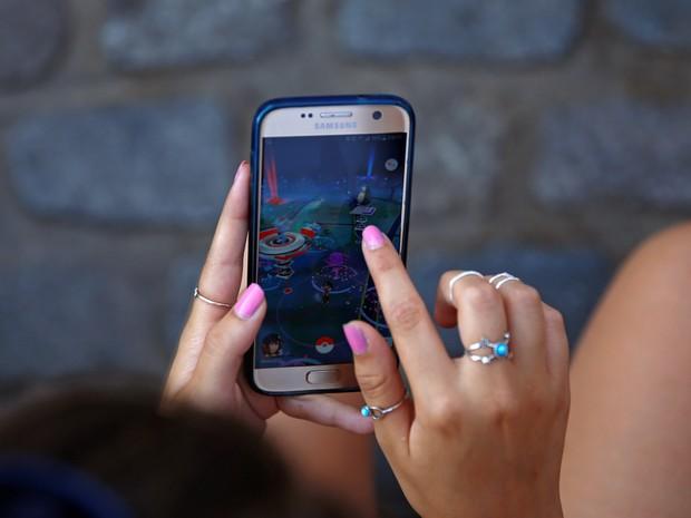 Uma mulher joga no aplicativo de realidade aumentada 'Pokemón Go' na praça Puerta del Sol em Madrid, na Espanha (Foto: Sérgio Perez/Reuters)