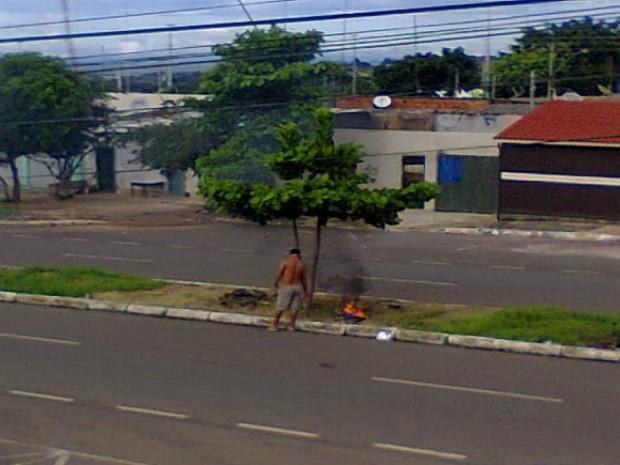 Homem queimando objetos em área verde em Santa Maria (Foto: Maria Terezinha/VC no G1)