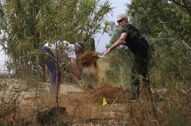 Integrantes da Scotland Yard cobrem buraco no solo neste sábado (7) durante buscas pela menina inglesa Madeleine McCann, desparecida em Portugal em 2007 (Foto: Carlos Vidigal/Reuters)