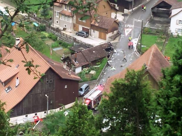 Imagem mostra destruição no vilarejo de Dittingen, na Suíça, depois que dois aviões que faziam apresentação colidiram (Foto:  REUTERS/Kantonspolizei Basel Landschaft/Handout via Reuters )