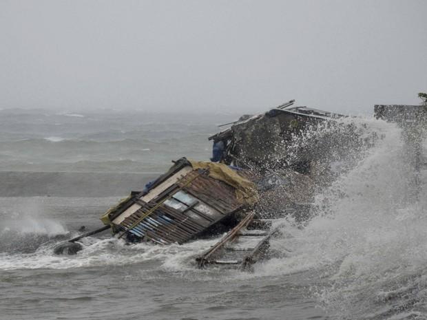 Casa é engolida por tempestade nesta sexta-feira (8) durante a passagem do supertufão Haiday pela cidade de Legazpi, ao sul de Manila, nas Filipinas (Foto: Nelson Salting/AP)