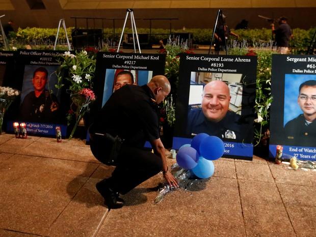 Um policial Dallas coloca balões e flores na frente das imagens dos 5 oficiais mortos durante no tiroteio de Dallas (Foto: REUTERS/Carlo Allegri)